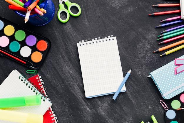 Papelería brillante en lío alrededor de cuaderno blanco sobre fondo gris Foto gratis