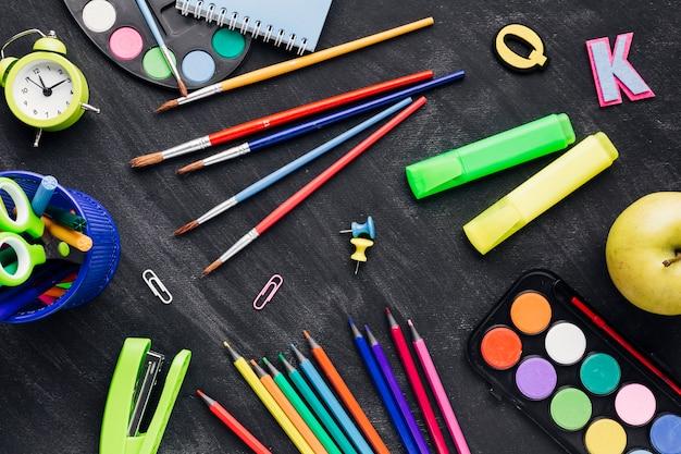 Papelería desordenada multicolor sobre fondo gris Foto gratis