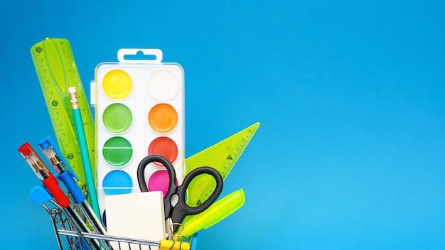 Papelería escolar en un carrito de compras de juguete sobre un fondo azul. el concepto de preparación para el comienzo del año escolar. copia espacio Foto gratis