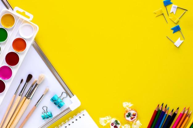 Papelería escolar de colores sobre fondo amarillo con copyspace. Foto gratis