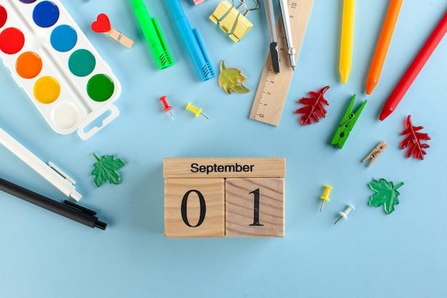 Papelería escolar sobre un fondo azul. calendario de madera 1 de septiembre. concepto del día del conocimiento. Foto Premium