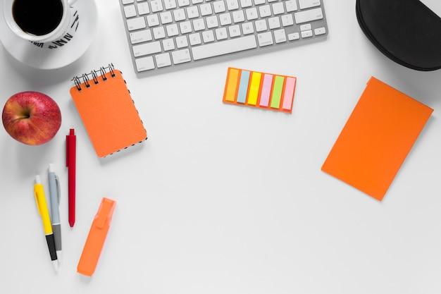 Papelerías coloridas con taza de café; manzana y teclado en escritorio blanco Foto gratis