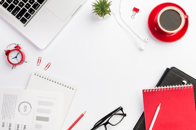 Papelerías de oficina con reloj despertador y taza de café en el escritorio blanco Foto gratis