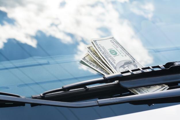 Paquete de billetes en dólares estadounidenses que quedan en un automóvil debajo del limpiaparabrisas en un parabrisas Foto Premium
