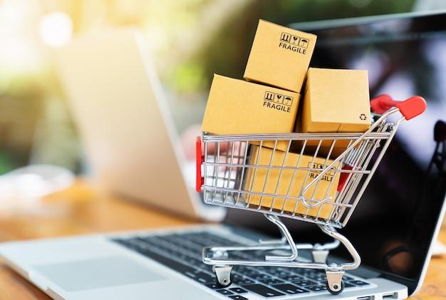 Paquete de cajas en el carrito con la computadora portátil para el concepto de compras en línea Foto Premium