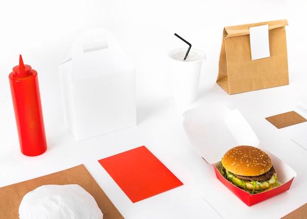 Paquete; hamburguesa; maqueta de salsa y vaso desechable sobre fondo blanco Foto gratis