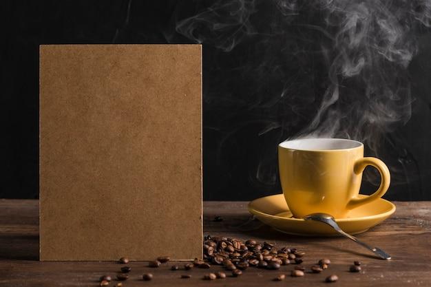 Paquete de papel y taza de café caliente. Foto gratis