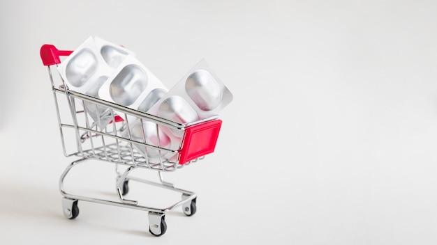 Paquete de píldoras de medicina en carrito de compras en miniatura sobre fondo blanco Foto gratis