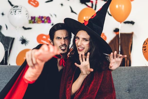 Par divertirse vistiendo disfraces de carnaval vestidos de halloween y maquillaje posando con murciélagos y globos en el fondo en la fiesta de halloween. concepto de celebración de vacaciones de halloween Foto Premium