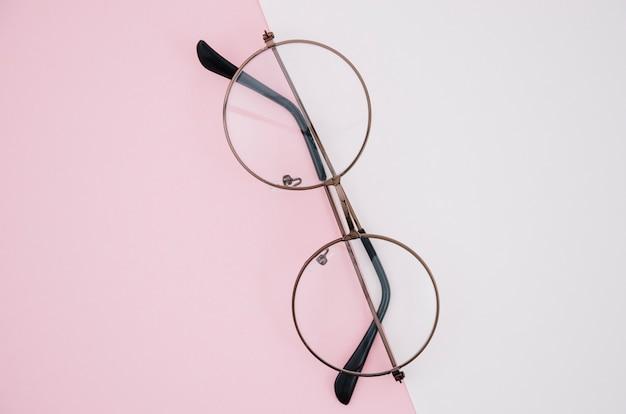 Par de gafas redondas sobre un fondo rosa y blanco Foto gratis