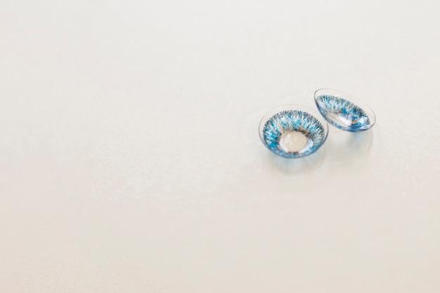 Par de lentes de contacto azules sobre fondo gris Foto gratis