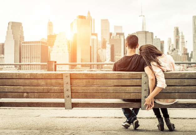 Par relajarse en el banco de nueva york frente al horizonte al atardecer. concepto sobre amor, relación y viaje Foto Premium