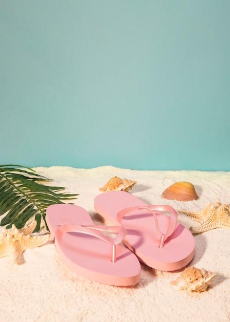 Par de sandalias rosas en la playa Foto gratis