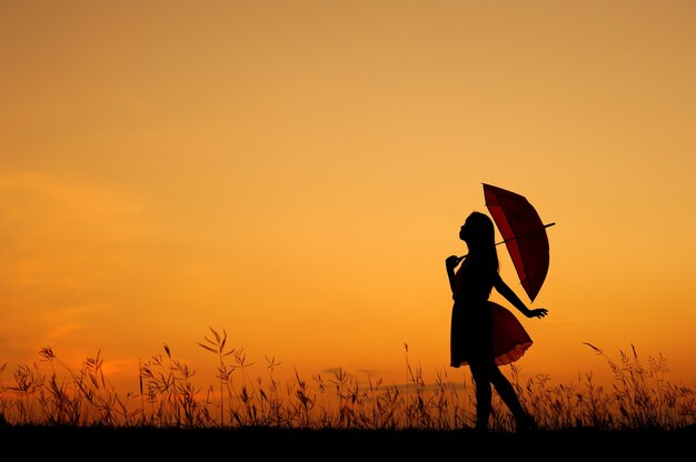 Paraguas Mujer De Pie Y Silueta Puesta Del Sol
