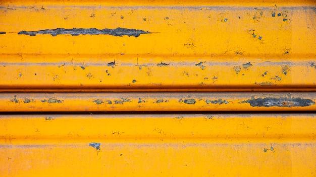 Pared metálica oxidada con pintura amarilla Foto gratis