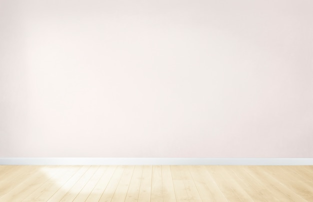 Pared rosa claro en una habitación vacía con piso de madera. Foto gratis