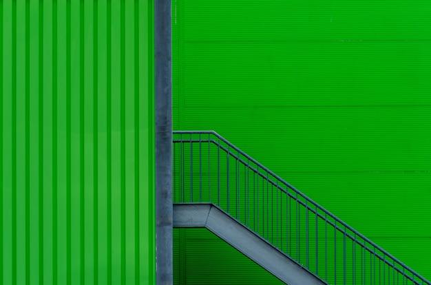 Pared verde con escaleras de metal Foto gratis