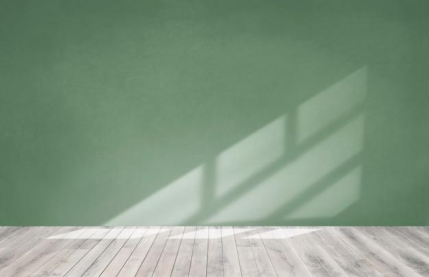 Pared verde en una habitación vacía con piso de madera. Foto gratis