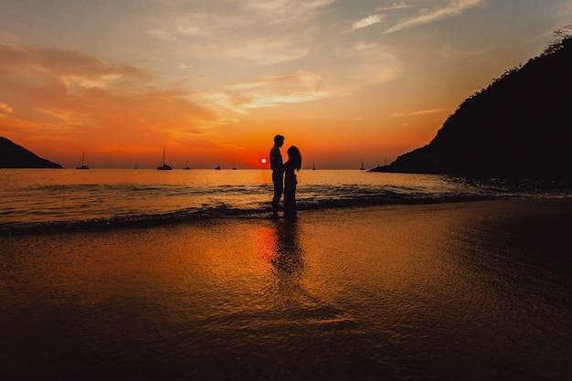 Pareja Abrazada En La Playa Al Atardecer
