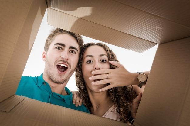 Pareja abriendo caja de cartón muy feliz Foto Premium