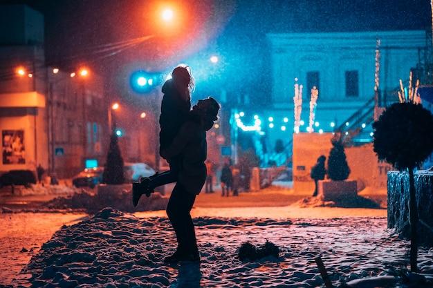 Pareja adulta joven en los brazos del otro en la calle cubierta de nieve Foto gratis