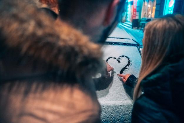 Pareja de adultos jóvenes dibuja un corazón en coche cubierto de nieve Foto gratis