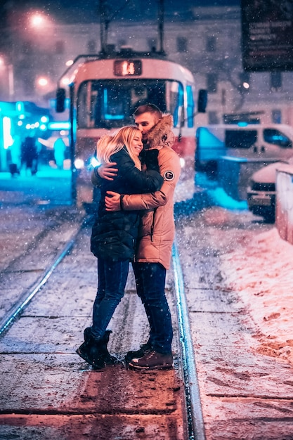 Pareja de adultos jóvenes en la línea de tranvía cubierto de nieve Foto gratis