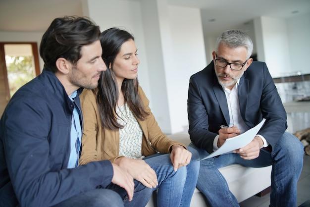 Pareja con agente inmobiliario mirando contrato en casa moderna Foto Premium