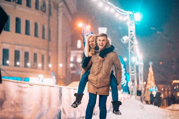 Pareja alegre y juguetona en trajes cálidos de invierno está jugando Foto gratis