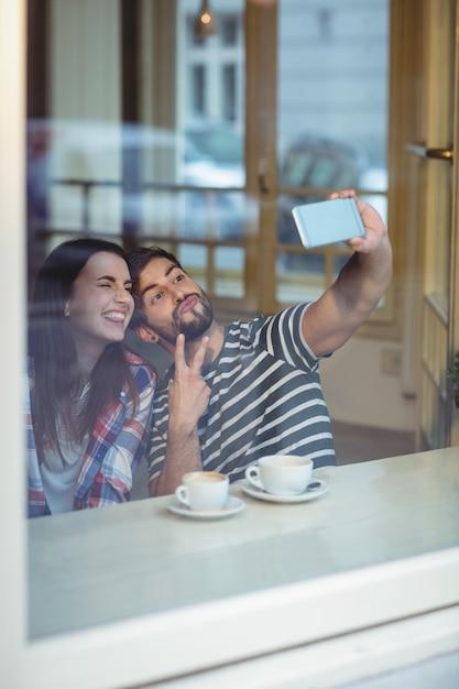 Pareja alegre tomando selfie en cafetería Foto Premium