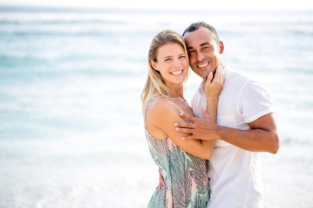 Pareja amorosa abrazando en la playa del mar de verano Foto gratis