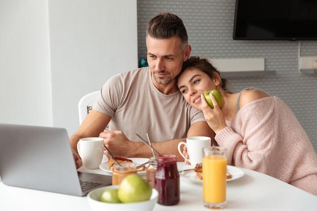 Pareja amorosa contenta desayunando mientras está sentado a la mesa y usando la computadora portátil en la cocina Foto gratis