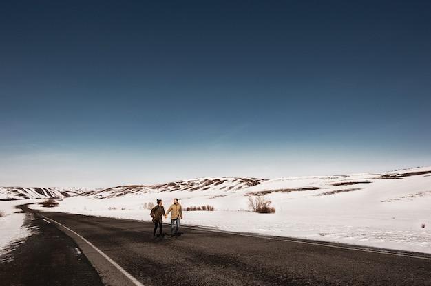 Pareja amorosa en el invierno corre en el camino entre las montañas. hombre y mujer corriendo por el camino. viaje de invierno. una pareja de enamorados viaja. Foto Premium
