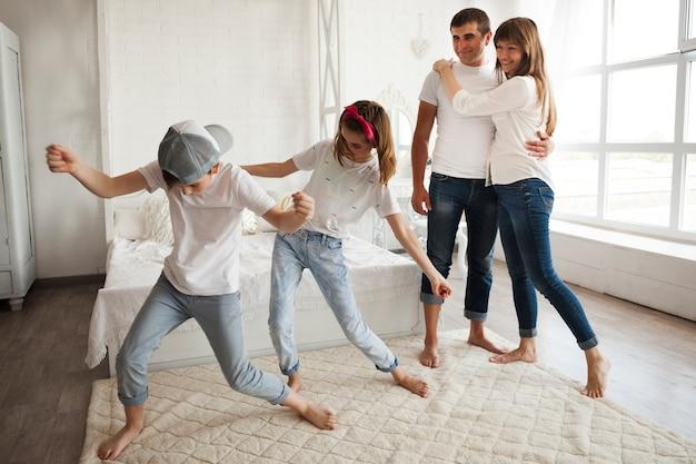 Pareja amorosa mirando el baile de sus hijos en casa. Foto gratis