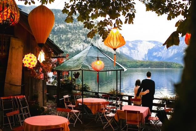 Pareja amorosa toma una hermosa tarde con linternas cerca del lago Foto gratis
