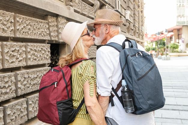 Pareja de ancianos besándose en la calle Foto gratis