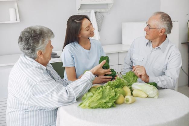 Pareja de ancianos en una cocina con joven nieta Foto gratis