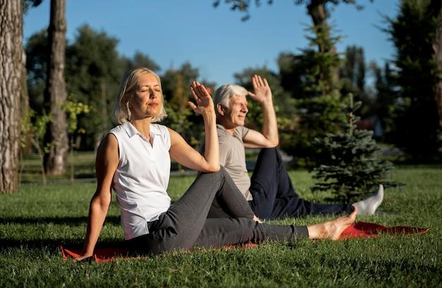 Pareja de ancianos haciendo yoga al aire libre Foto gratis