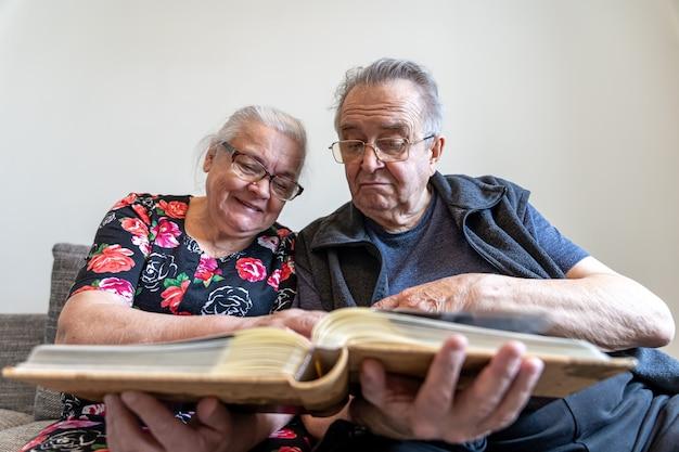 Una pareja de ancianos está mirando fotografías en un álbum de fotos familiar. Foto gratis