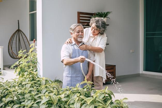 Pareja de ancianos regando una flor en casa jardín Foto gratis