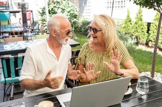 Pareja de ancianos riéndose juntos delante de una computadora portátil Foto gratis