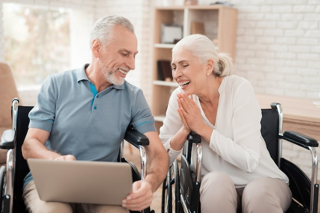 Pareja de ancianos en silla de ruedas mira la pantalla del portátil. Foto Premium