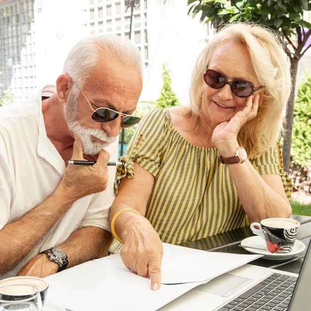 Pareja de ancianos tomando notas en la agenda Foto gratis