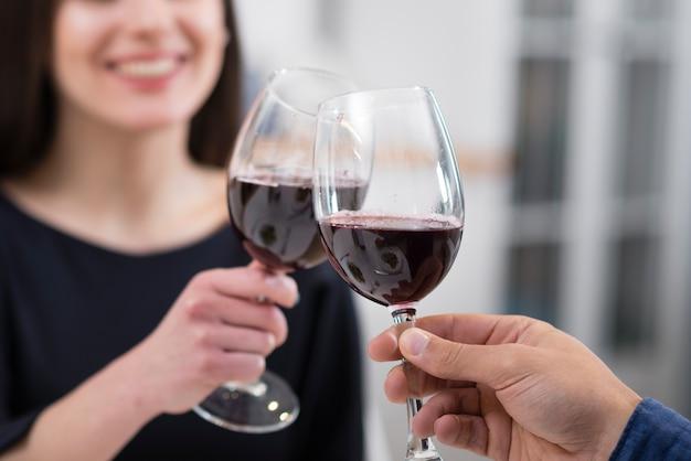 Pareja animando con copas de vino close-up Foto gratis