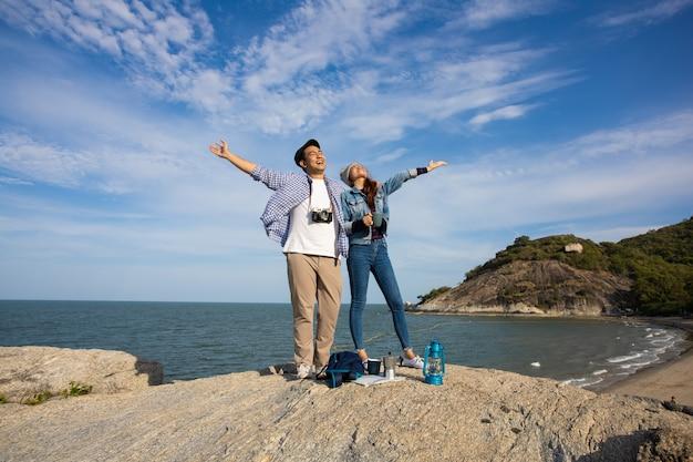 Pareja asiática en camisa azul con taza de café y picnic de cámara vintage en la montaña cerca de la playa vista al mar feliz y cara de sonrisa Foto Premium