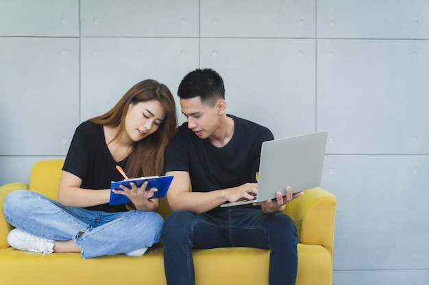 La pareja asiática feliz joven del onwer del sme del negocio en ropa de sport con la cara sonriente está utilizando el ordenador portátil y está comprobando el producto en existencia y escribe en el tablero en su oficina en casa de lanzamiento, vendedor de la entrega Foto Premium