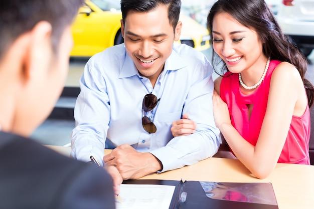 Pareja asiática firma contrato de venta de coche en concesionario Foto Premium