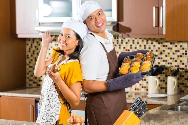 Pareja asiática hornear magdalenas en la cocina de casa Foto Premium
