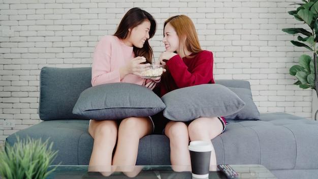 Pareja asiática lesbiana viendo la televisión reír y comiendo palomitas de maíz en la sala de estar en casa, dulce pareja disfruta Foto gratis