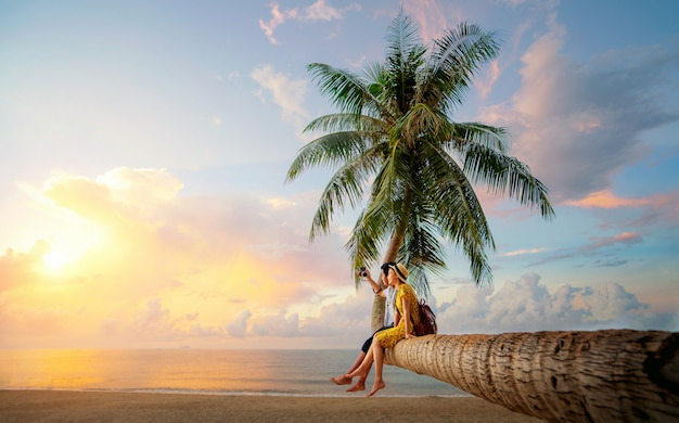 Pareja asiática en palmera de coco en la isla de kho mak Foto Premium